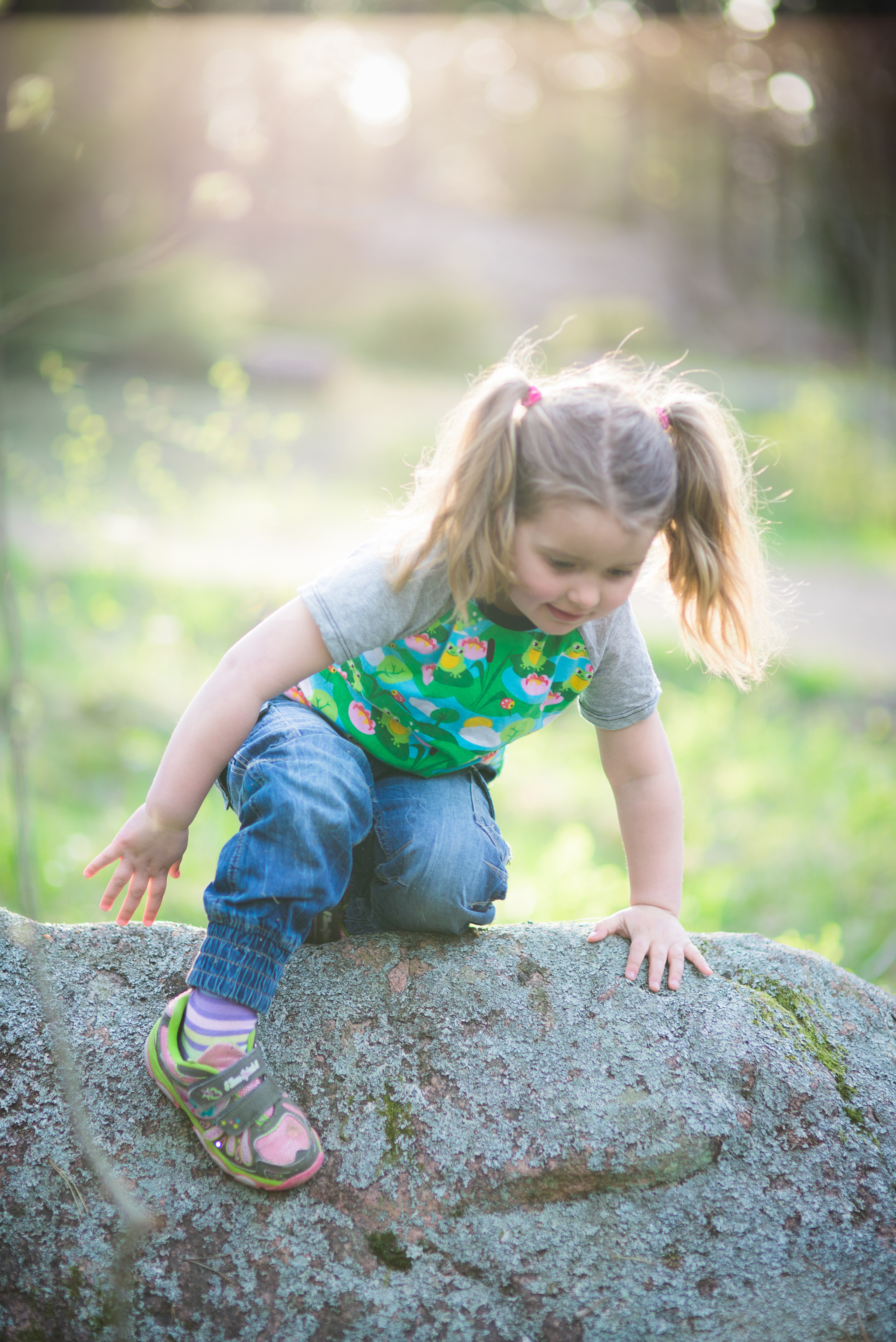 girl climbing on a rock in the woods