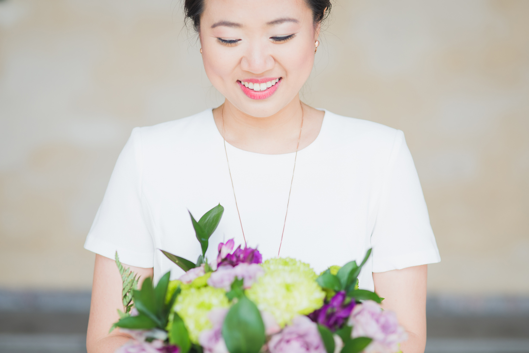 smiling bride looking at wedding bouquet