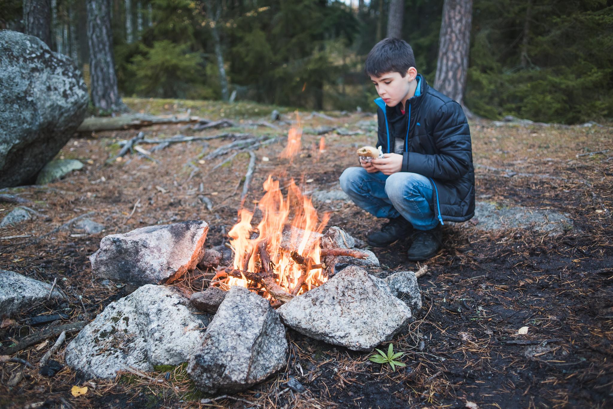 pojke ater matsack vid elden