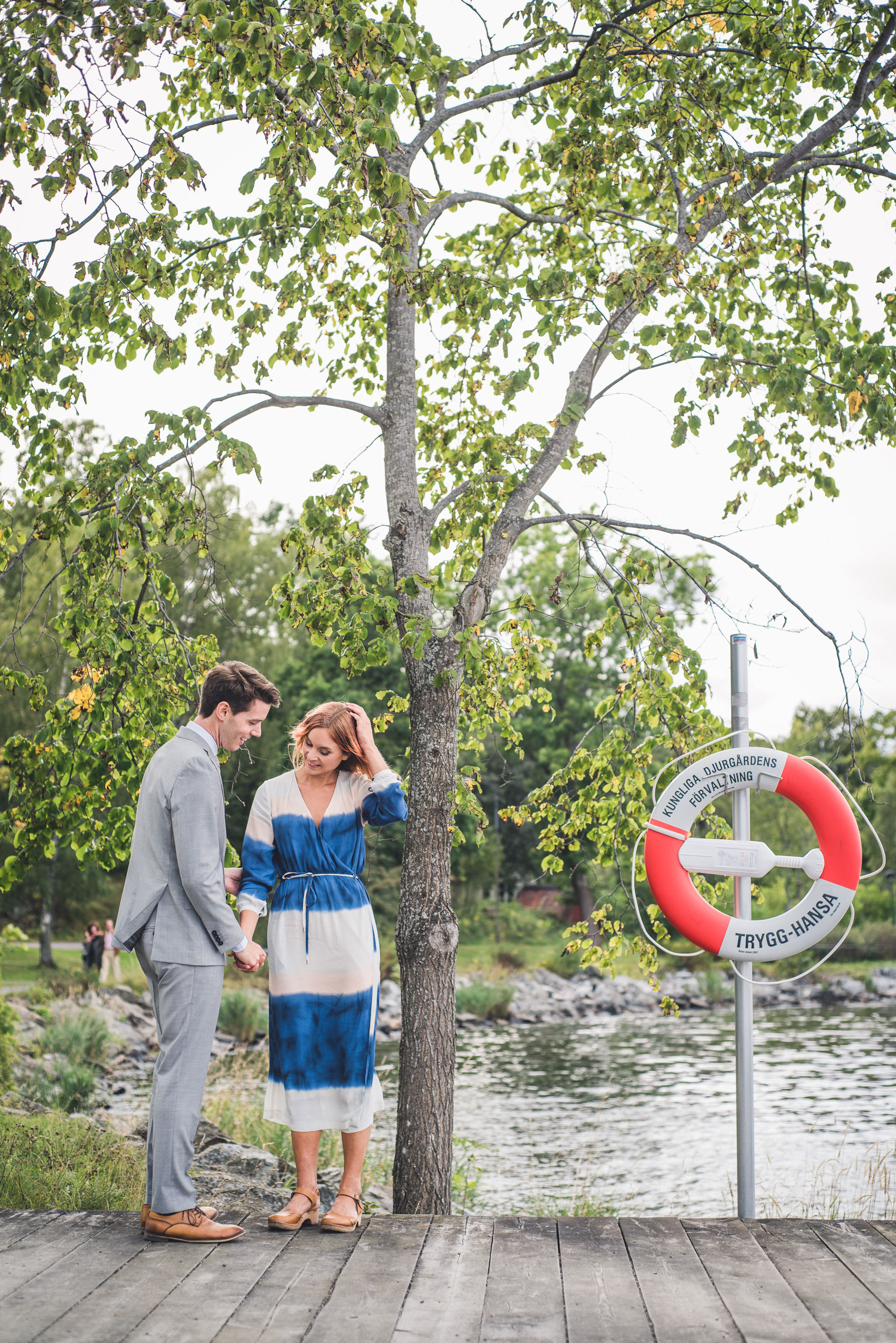 the bridal couple next to a tree and a lifebuoy