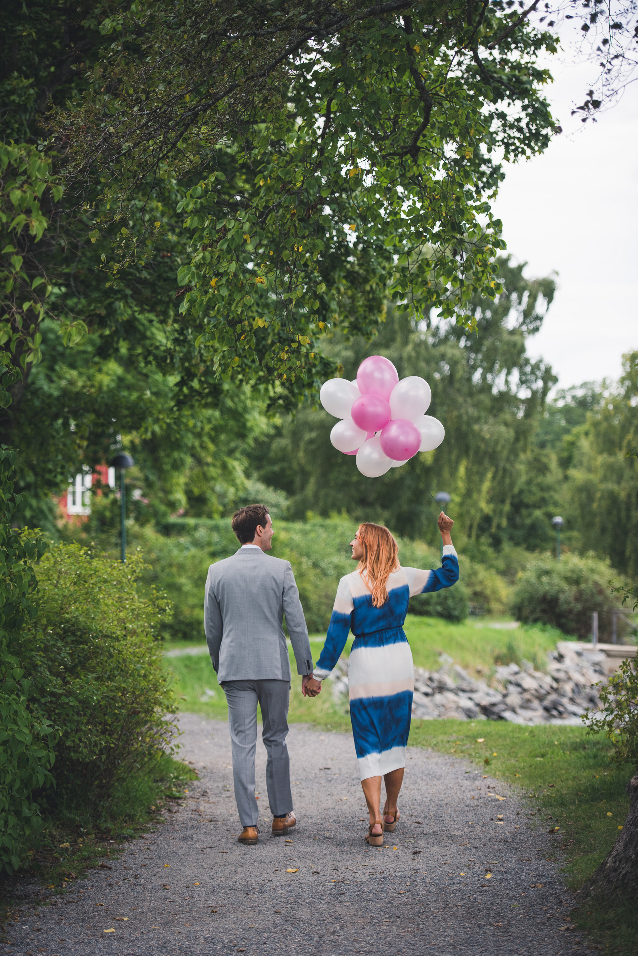 the newlyweds walking away with balloons